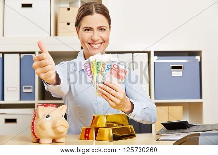 Smiling successful woman with money and gold holding her thumbs up
