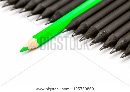 Green pencil standing out from the row of black pencils.
