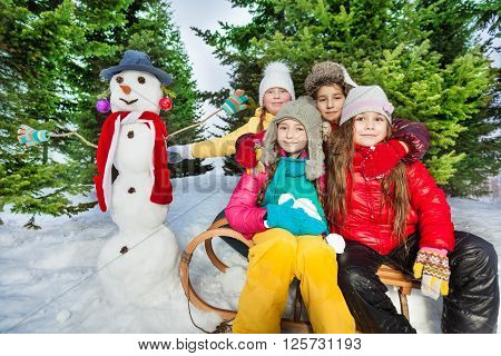 Four friends sitting on the wooden sledge near cute snowman with red scarf at the fir forest