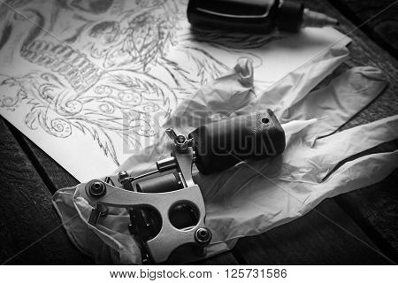 Tattoo machine, sketch and tattoo supplies, on old wooden table. Retro stylization
