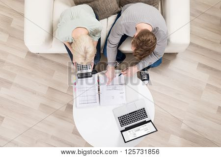 Young Couple Analyzing Invoices