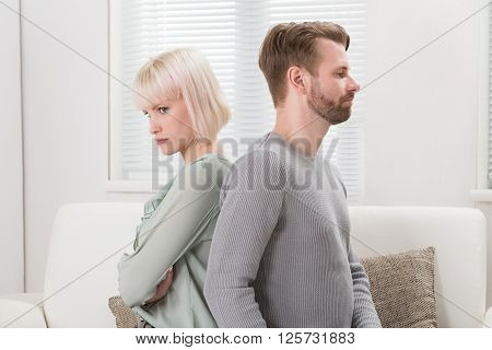 Couple Sitting Back To Back On Couch