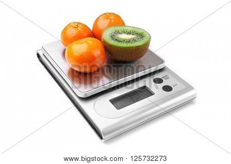 Kiwi and tangerines on digital kitchen scales, isolated on white