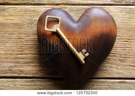 Golden key with brown heart on wooden background