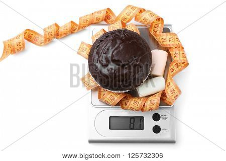 Chocolate cupcake with marshmallow and centimeter on digital kitchen scales, isolated on white