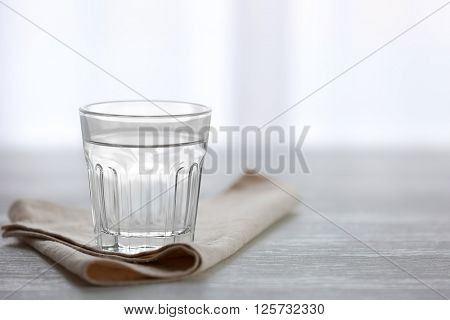 Glass of water with napkin  on wooden background