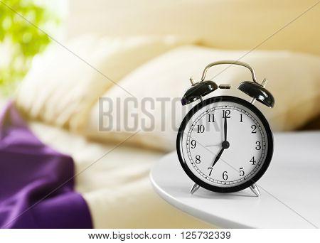 Vintage alarm clock on bedside table in a room