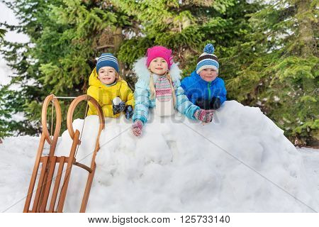 Group of little kids play in snowball fight in the snow fortress in the park