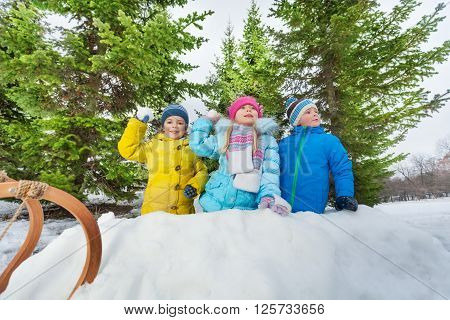 Children boys and girls behind snow fortress wall throw snowballs