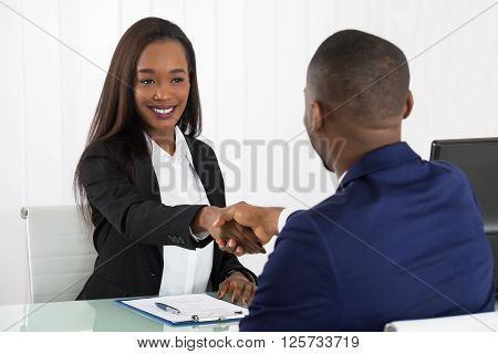 Two Businesspeople Shaking Hands At Office