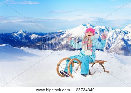 Little girl on sledge in the mountains with lifted hands