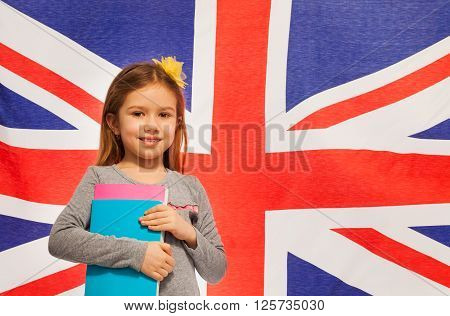 Smiling English schoolgirl standing with  textbooks, flag of Great Britain at the background