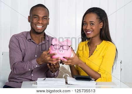 Happy Couple Holding Piggybank