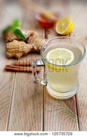 Ginger lemon honey mint leaves on wood background. A cup of ginger tea