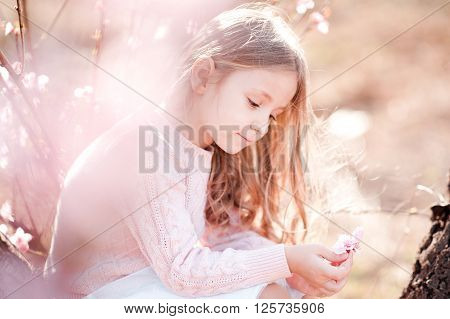 Cute kid girl 4-5 year old holding peach flower outdoors. Playful. Childhood.