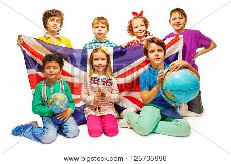 Group of seven happy kids studying geography with globes and holding flag of Great Britain, isolated on white