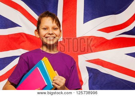 Happy English student standing with textbooks under his arm, flag of Great Britain behind