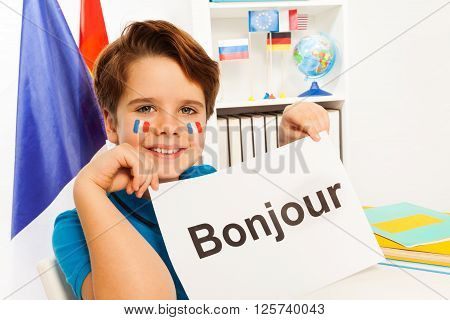 Smiling French boy holding sheet of paper with printed word bonjour - hello in French- at the classroom