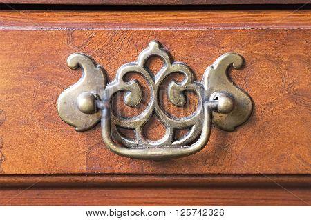 Old door knocker on wooden door close up