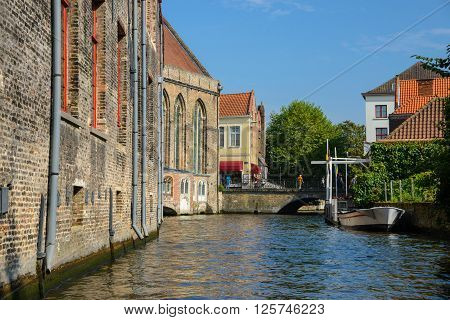 View from the canal to the bridge boat and old brick merchant houses in Bruges Belgium. Ancient medieval europe city view.