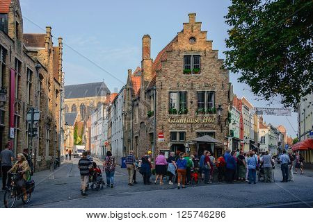 BRUGES BELGIUM - September 19 2014: Restaurant in Bruges old city. Lots of people from touristic groups walking on the street.