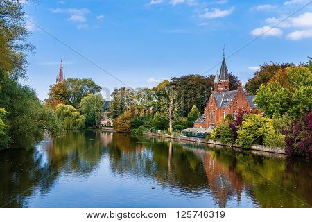 Colorful reflections of trees in the water in Minnerwater park. Bruges Belgium