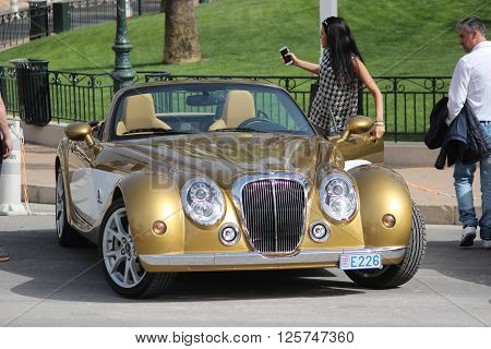 Monte-Carlo Monaco - April 6 2016: Young Woman Driving a Golden Mitsuoka Roadster near the Monte-Carlo Casino in Monaco