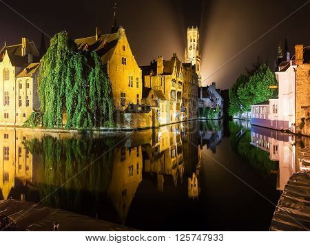 Medieval european city Brugge in lights by night reflected in the water