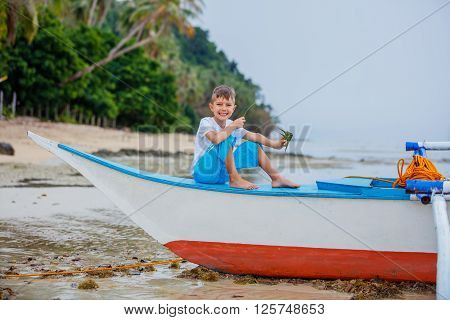 Little boy sitting in boat lying on the beach dreems of the sea