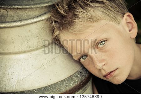 Blue Eyed Boy Leans Head Against Metal Container