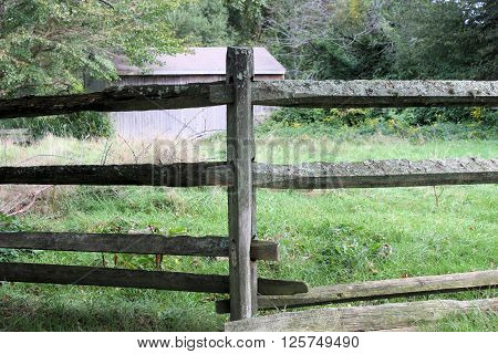 Split rail fence bordering an overgrown lot on a cloudy day.