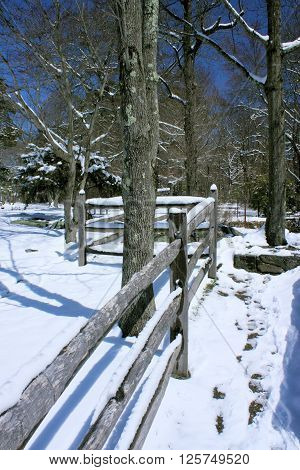 Plank fence border at a park after an early spring snowstorm.