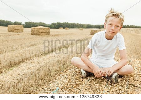 Boy Sits Alone In Harvested Wheat Field