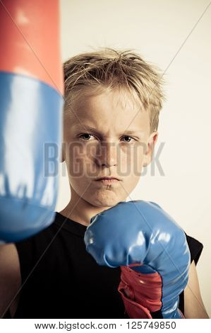 Frowning Boy Wearing Black Shirt And Boxing Gloves