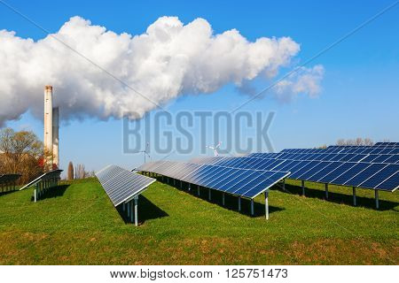 field with solar collectors fossil-fuel power station and wind turbines in