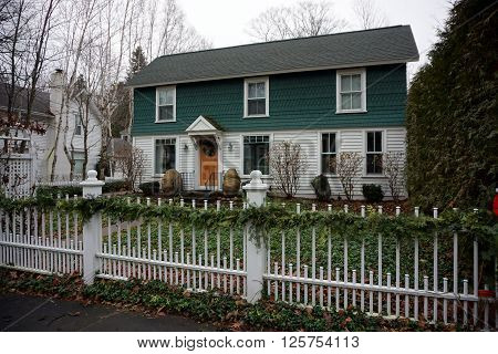 HARBOR SPRINGS, MICHIGAN / UNITED STATES - DECEMBER 23, 2015: A white metal picket fence, decorated with a Christmas garland, in front of a home in Harbor Springs.