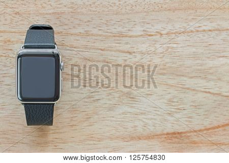 Smart watch with leather bands on wooden background with copyspace