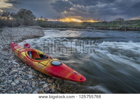 whitewater kayak and river rapid at sunset - Cache la Poudre River in Fort Collins, Colorado