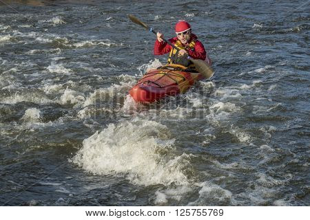 whitewater kayaker paddling upstream the river rapid