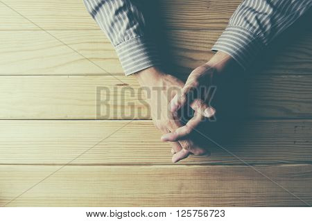 Close up on male hands folded in prayer at a wooden table