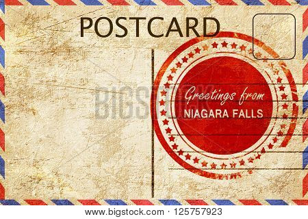 greetings from niagara falls, stamped on a postcard