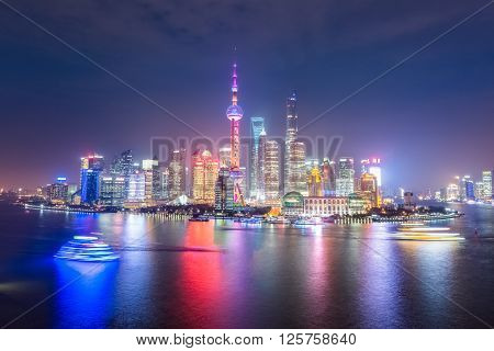 beautiful shanghai skyline at night light trails from cruise ship in huangpu river China.