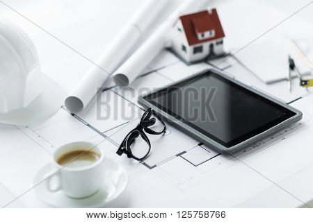 architecture, building, construction, real estate and home concept - close up of living house model and tablet pc computer screen at office