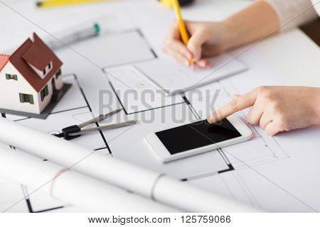 business, architecture, building, construction and people concept - close up of architect hand with living house blueprint and smarphone writing to notebook