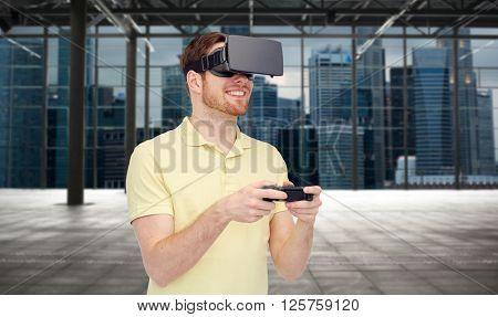 3d technology, virtual reality, entertainment and people concept - happy young man with virtual reality headset or 3d glasses playing with game controller gamepad over empty industrial room