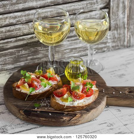 Tomato and cheese bruschetta and two glasses of white wine on a rustic wooden cutting board. Healthy breakfast snack or appetizer with wine