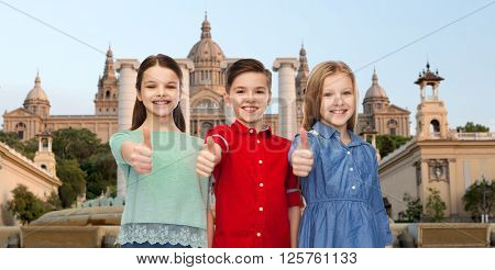 childhood, gesture, travel, tourism and people concept - happy smiling boy and girls showing thumbs up over national museum of barcelona background
