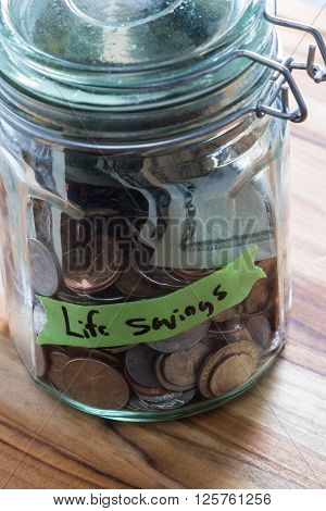close up of a jar with money and a label using green tape and a black marker