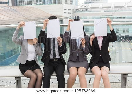 group of business people hold a blank paper to hide their face