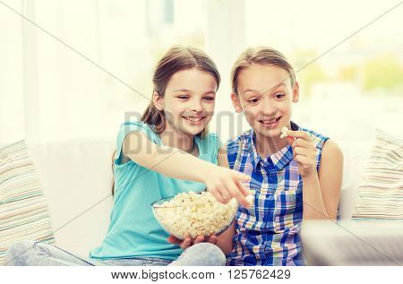 people, children, television, friends and friendship concept - two happy little girls watching tv and eating popcorn at home